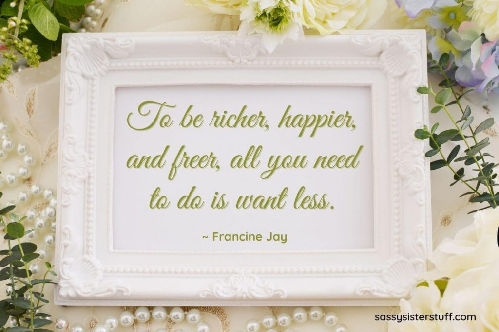 an ornate white frame with a quote about being happier with less and pearls and flowers around the frame