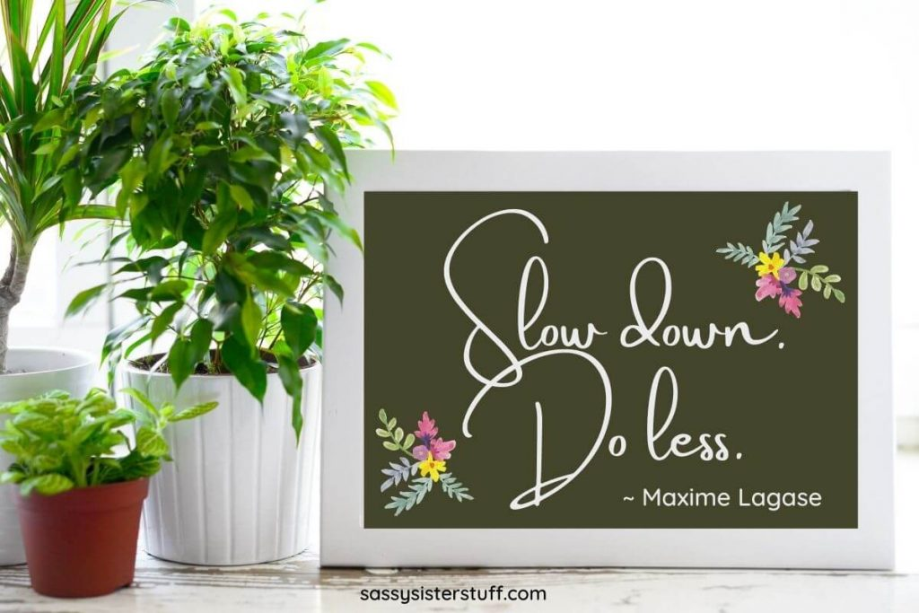 potted plants and a framed quote about how to life a simple life and be happy