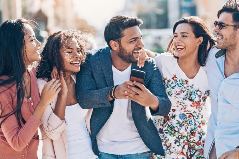 a group of five friends walking together laughing and showing how to improve social wellness